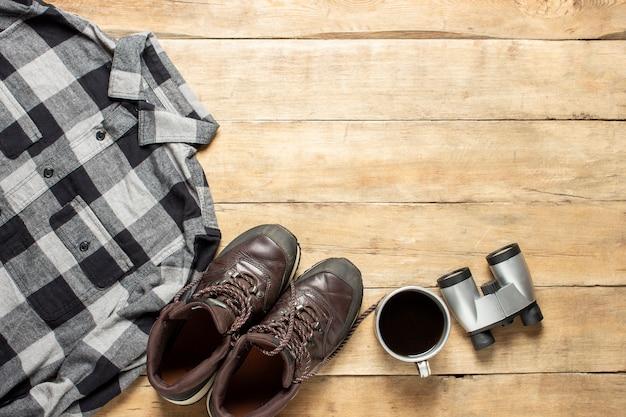 Stivali per una scia, camicia, tazza di tè, binocolo su un fondo di legno. concetto di escursionismo, turismo, campo, montagne, foresta.