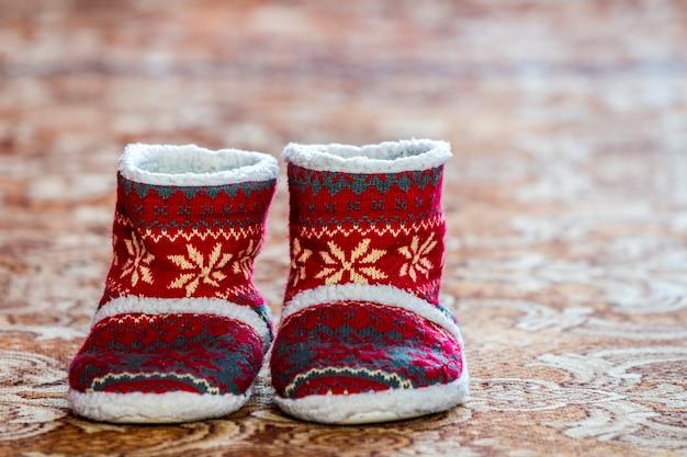 Stivali rossi di natale di inverno con il modello dell'ornamento