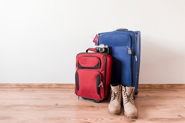 Stivali vicino a valigie e macchina fotografica