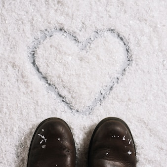 Stivali vicino al cuore dipinto sulla neve