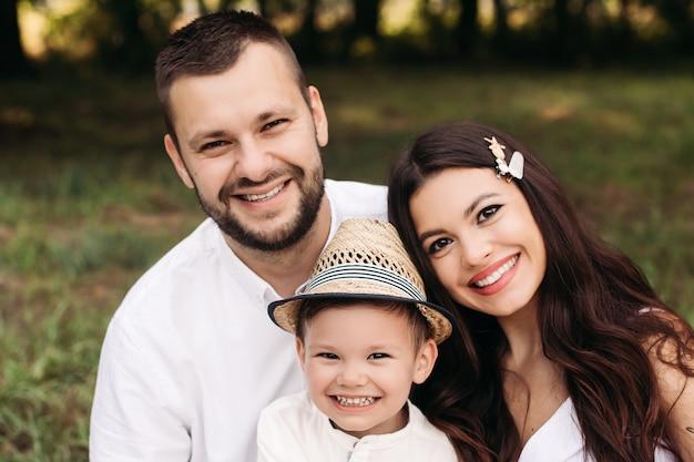Stock photo headshot di una bella famiglia caucasica di madre, padre e figlio che sorridono felicemente alla telecamera nel parco il giorno d'estate.
