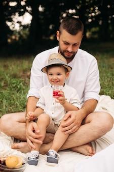 Stock photo ritratto di un ragazzino felice in cappello estivo bere succo da un bicchiere seduto con suo padre barbuto sulla coperta al picnic il giorno d'estate.