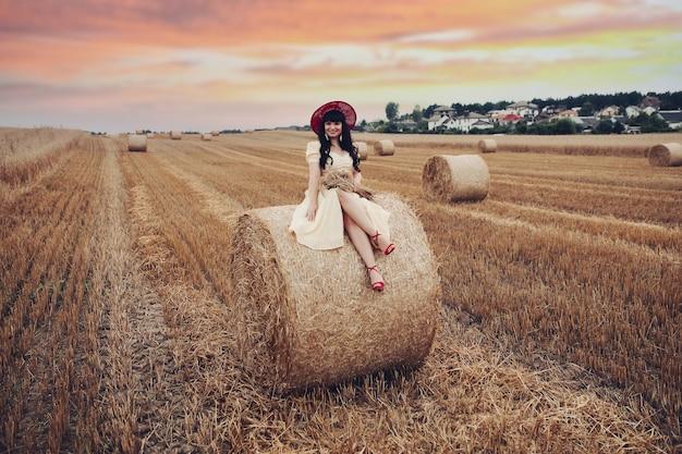 Stock photo ritratto di una bella ragazza dai capelli scuri in abito e cappello con un mazzo di spighette seduto sul pagliaio nel campo di grano al tramonto.