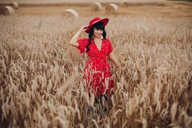 Stock photo ritratto di una splendida donna adulta con lunghi capelli scuri che indossa un abito rosso brillante a pois e cappello rosso sorridente