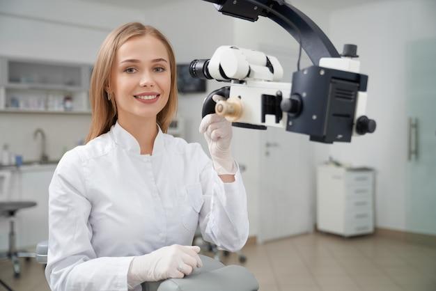 Stomatologo che posa in odontoiatria vicino al microscopio dentale.