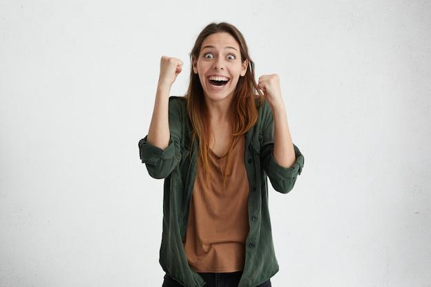 Stordisci bella donna in abiti casual che celebra la sua vittoria alzando le mani stringendo i pugni avendo felicità e soddisfazione.
