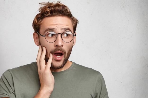 Stordito, scioccato uomo barbuto con la mascella aperta, ascolta una storia incredibile,