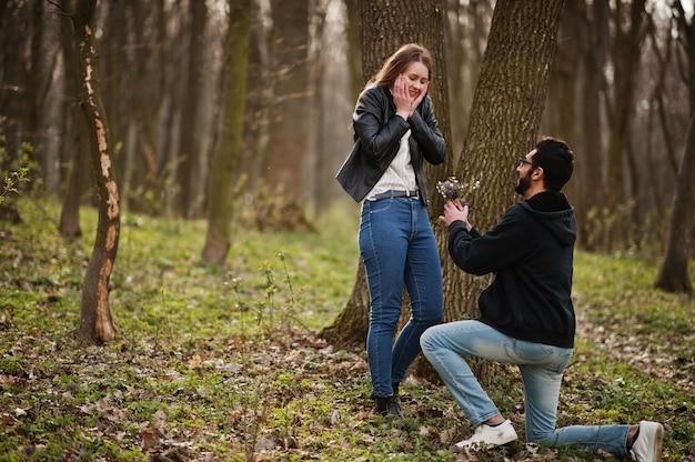 Storia d'amore di cool coppia multirazziale nella foresta di primavera. proposta di matrimonio uomo arabo con ragazza europea.