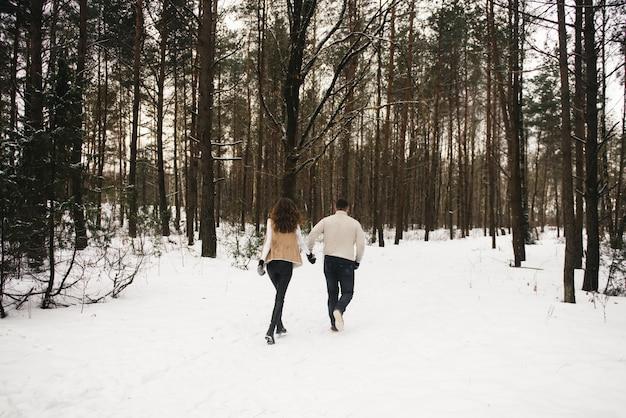 Storia d'amore invernale sul ghiaccio. ragazzo e ragazza alla moda con passeggiata nella foresta innevata. romanza