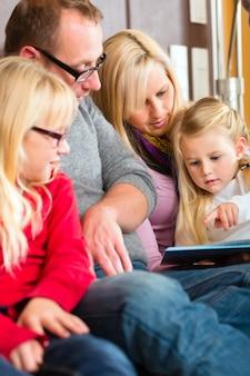 Storia della lettura della famiglia in libro sul sofà nel paese