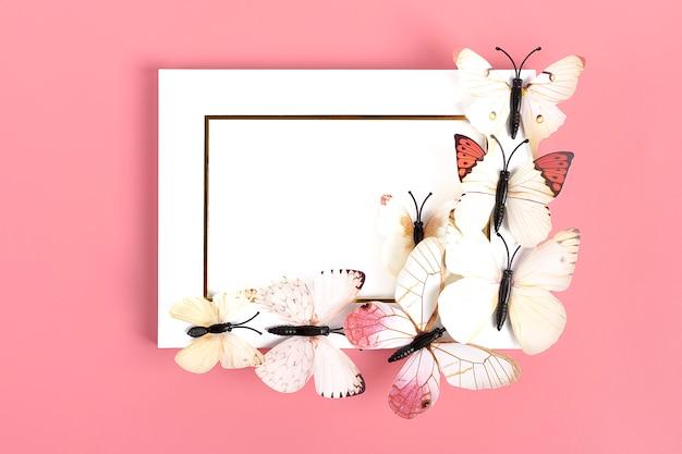 Stormo di farfalle sulla cornice bianca su sfondo rosa