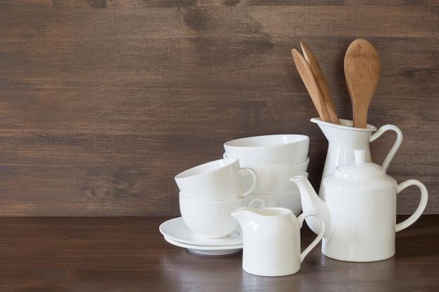 Stoviglie, argilla, utensili bianchi e altre cose diverse sul tavolo di legno.