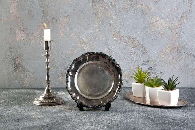 Stoviglie d'argento d'annata su fondo concreto