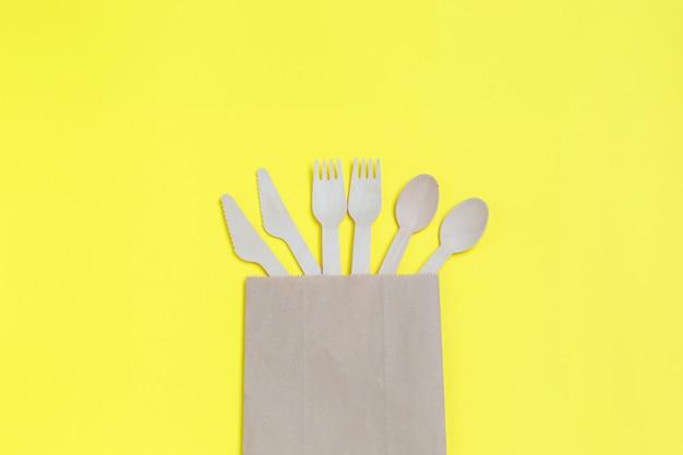 Stoviglie da materiali naturali, cucchiai di legno, coltelli e forchette in sacchetto di carta su sfondo giallo.