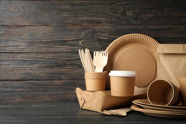 Stoviglie ecologiche e sacco di carta sulla tavola di legno, spazio della copia