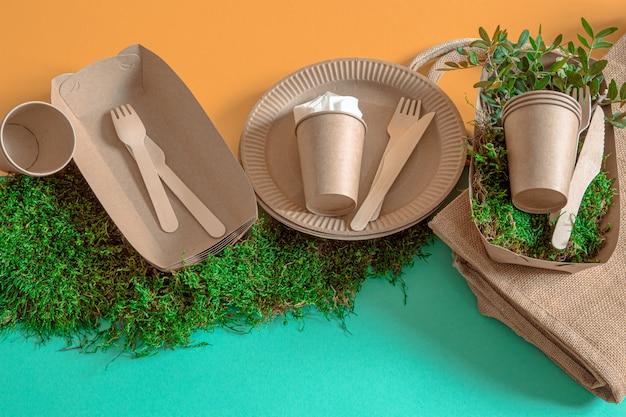 Stoviglie ecologiche, usa e getta, riciclabili su uno sfondo colorato.