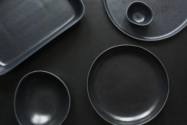 Stoviglie, posate, utensili neri e cose diverse su tavolo nero.
