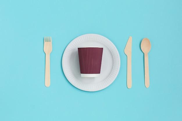 Stoviglie usa e getta da materiali naturali, cucchiaio di legno, forchetta, coltello, ciotola di carta con bicchiere di carta sul blu