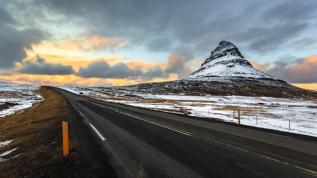 Strada a kirkjufell sotto il cielo nuvoloso al crepuscolo
