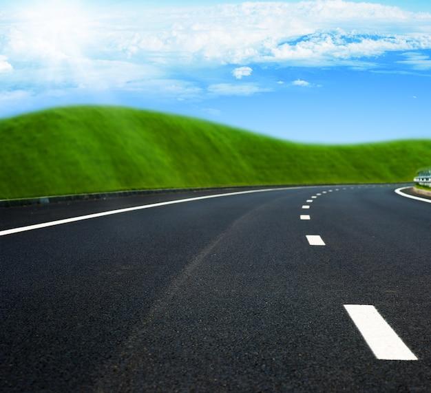 Strada asfaltata attraverso il campo e le nuvole verdi su cielo blu nel giorno di estate