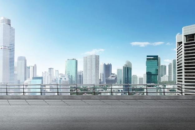 Strada asfaltata con edificio moderno e grattacieli