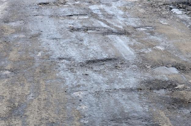 Strada asfaltata danneggiata con buche causate da cicli di congelamento e scongelamento durante l'inverno