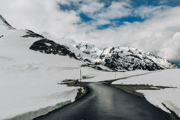 Strada asfaltata in montagne nevose delle alpi nell'ora legale