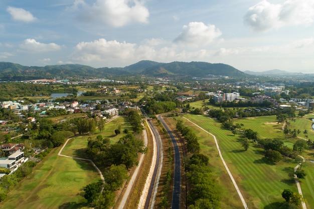 Strada asfaltata intorno alla foto verde del campo da golf dal colpo del drone di vista aerea.