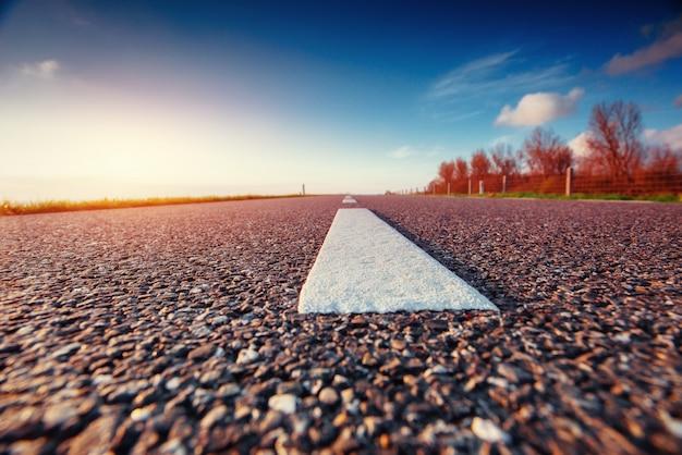 Strada asfaltata lungo il mare al tramonto
