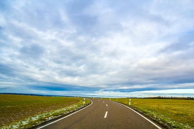 Strada asfaltata nera vuota tra i campi verdi
