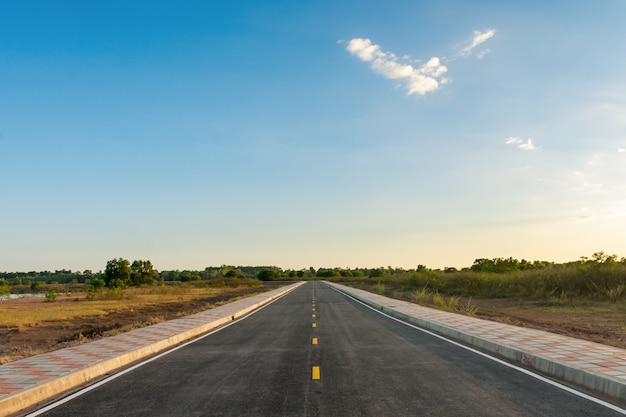 Strada asfaltata vuota e cielo blu pulito nel fondo di giorno di estate con lo spazio della copia