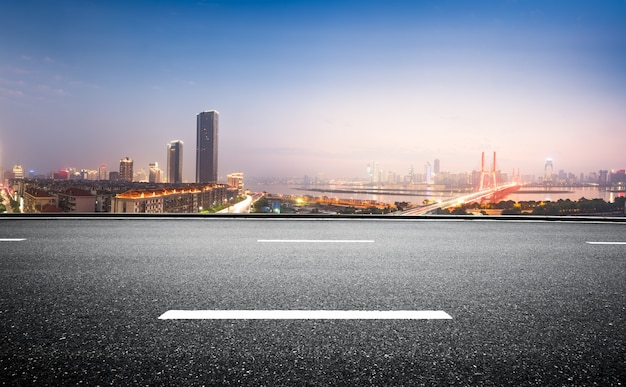 Strada asfaltata vuota e skyline moderno di notte
