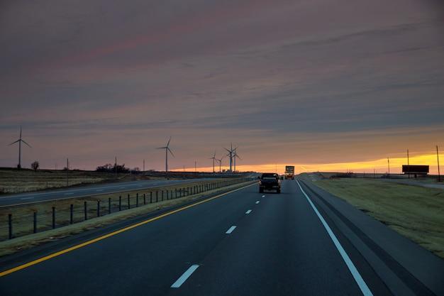 Strada che conduce alla vista delle fattorie di turbine eoliche del texas