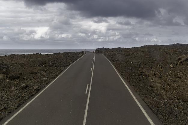Strada circondata da colline sotto un cielo nuvoloso nel parco nazionale di timanfaya in spagna