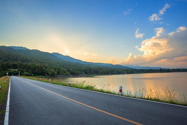 Strada con vista panoramica del serbatoio huay tueng tao con foresta di montagna al tramonto sera