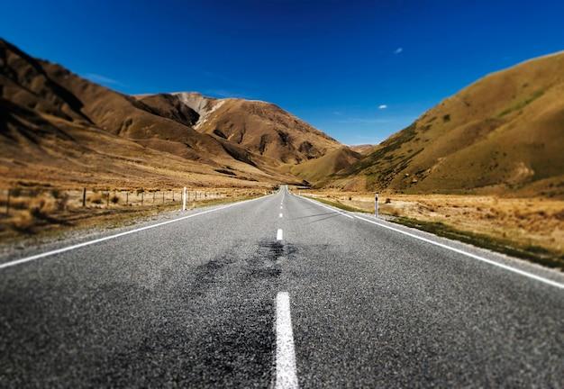 Strada continua in un scenico con le catene montuose concetto di afar