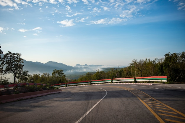 Strada della curva che conduce un'automobile sulla strada della montagna in discesa. bella nuvola drammatica del cielo blu della curva con la nebbia della foschia di mattina.