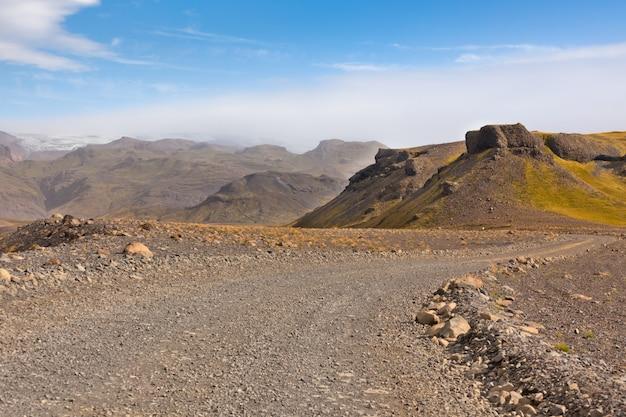 Strada di ghiaia attraverso il paesaggio islandese delle montagne di lava. colpo orizzontale