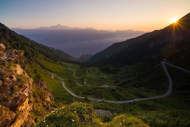 Strada di montagna che porta al passo di alta montagna in italia. vista espasiva al tramonto, alpi italiane.