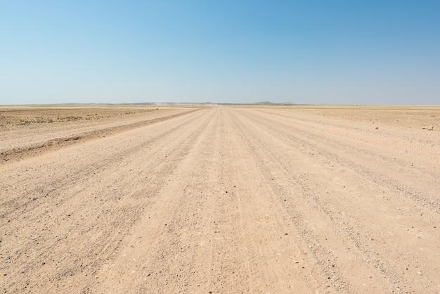 Strada diritta della ghiaia che attraversa il deserto variopinto di namib, nel maestoso parco nazionale di namib naukluft, migliore destinazione di viaggio in namibia, africa.