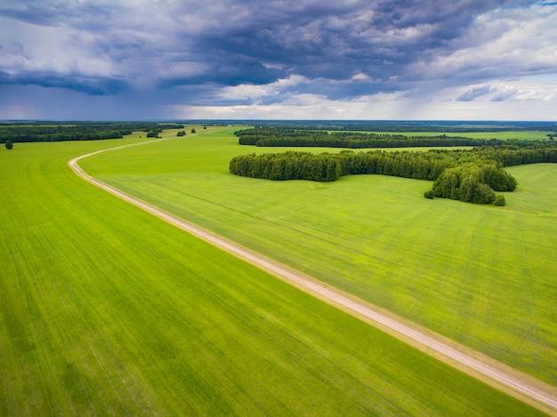 Strada e campi contro il cielo con nuvole prese da un quadrocopter