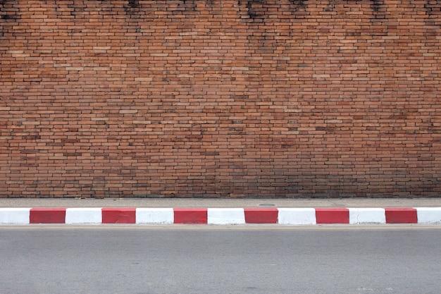Strada e vecchia struttura rossa del muro di mattoni