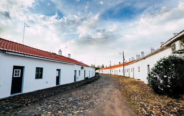 Strada in pietra con facciate bianche e camini