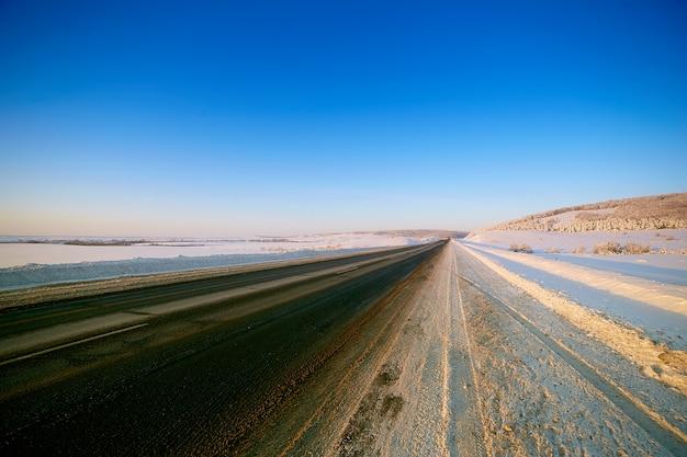Strada invernale attraverso campi innevati e foreste