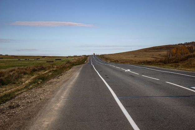 Strada larga con segnaletica in mezzo al campo