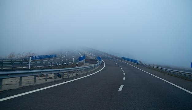 Strada nebbiosa con nebbia nell'orizzonte