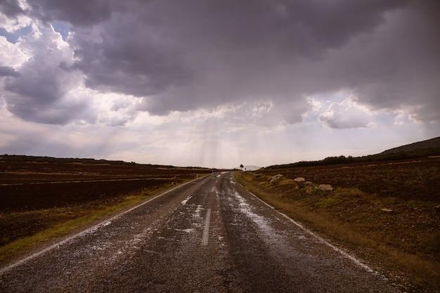 Strada nel mezzo di campi erbosi asciutti in una giornata nuvolosa