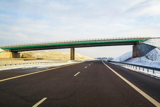 Strada principale asfaltata vuota larga moderna moderna che allunga all'orizzonte sotto l'alto ponte che gira a destra oltre la foresta distante al giorno. velocità, viaggio confortevole e concetto di costruzione stradale professionale.