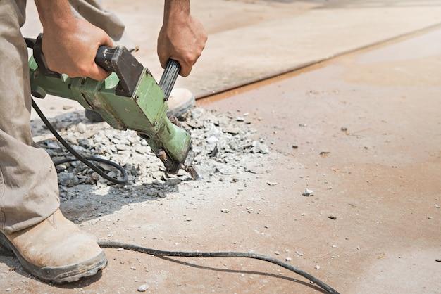 Strada privata concreta di perforazione del lavoratore con il martello pneumatico.