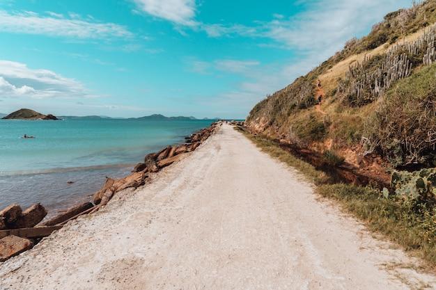 Strada ricoperta di sabbia circondata dal mare e da rocce sotto un cielo blu a rio de janeiro